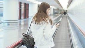 发短信在移动的走道的电话的后侧方视图europian妇女在国际机场 股票录像