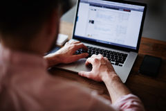 发短信在计算机上的年轻男学生坐在木桌上 免版税库存图片