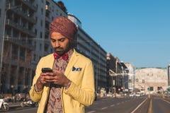 发短信在都市上下文的印地安英俊的人 图库摄影