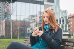 发短信在长凳的美丽的女孩 库存照片