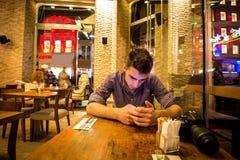 发短信在餐馆的年轻成人人 免版税库存照片