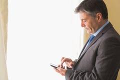 发短信在他的手机的体贴的人 免版税库存图片