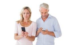 发短信在他们的智能手机的愉快的夫妇 库存照片