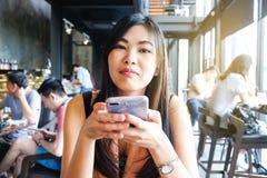 发短信在moblie的妇女打电话,当坐在现代咖啡馆时 库存图片