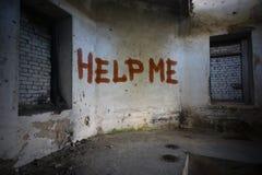 发短信帮助我在肮脏的老墙壁上在一个被放弃的房子里 库存照片