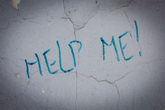 发短信帮助我在肮脏的老墙壁上在城市街道 库存照片
