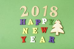 发短信给在字母表五颜六色的块写的绿色背景的新年快乐2018年  节假日概念 库存照片