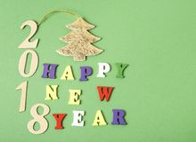 发短信给在字母表五颜六色的块写的绿色背景的新年快乐2018年  节假日概念 免版税库存图片