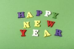 发短信给在字母表五颜六色的块写的绿色背景的新年快乐  节假日概念 免版税库存照片