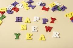 发短信给在字母表五颜六色的块写的黄色背景的新年快乐  节假日概念 免版税库存图片