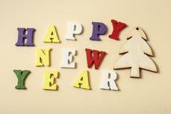 发短信给在字母表五颜六色的块写的黄色背景的新年快乐  节假日概念 库存照片