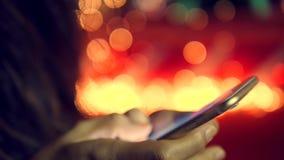 发短信给在巧妙的手机的女性手问候消息有圣诞树在背景的Bokeh光的 4K 股票录像