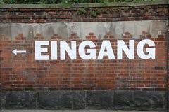 发短信给在意味出口用德语的砖墙上的EINGANG 库存照片