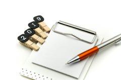 发短信给在笔记本的2019个目标有在白色背景,新年概念的笔的 免版税库存图片