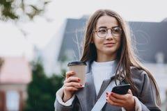 发短信给或使用智能手机的年轻女人 免版税库存照片
