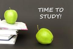 发短信给时刻学习,两个绿色苹果,与概念的开放书 库存图片