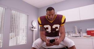 发短信非裔美国人的足球运动员,当等待在hosp时 库存图片