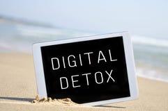 发短信给在一台片剂计算机的数字式戒毒所,在海滩的沙子 库存图片