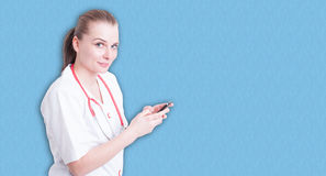 发短信给在手机的年轻女性医生一则消息 免版税库存照片
