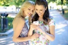 发短信给他们的女朋友的两名妇女 免版税库存图片
