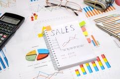发短信给销售在有分析图表和图的笔记本 免版税库存照片