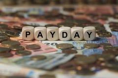 发薪日-与信件,金钱区段期限的立方体-与木立方体的标志 免版税库存照片
