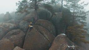 发表看法在人坐岩石的上面在用雾盖的冬天山的 影视素材