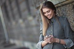 发送微笑的sms妇女 库存照片