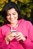 发送或读sms的愉快的妇女在移动电话 库存图片