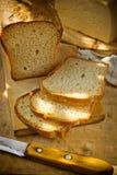 发酵母全麦面包大面包切开了成切片,金黄外壳,乳酪,亚麻制毛巾,木厨房用桌大块  免版税库存照片