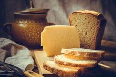 发酵母大面包切了在木切板,乳酪,黏土餐具,刀子,农村厨房内部大块的面包  免版税库存照片
