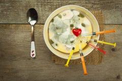 发霉的布丁和注射器 疾病的治疗 模子和抗生素 充分毒食物模子 不健康的食物 免版税库存照片