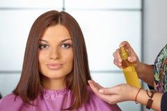 发廊。妇女理发。对化妆油的用途。 库存照片