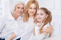 取决于她的母亲和祖母的小微笑的女孩 免版税库存图片