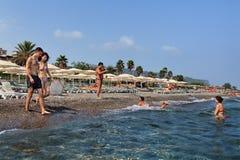 取暖在海滩的海水的度假者与遮阳伞和deckc 免版税库存图片