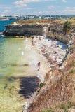 取暖在Chersone古城的一个狂放的海滩的游人 库存照片