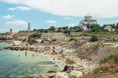 取暖在Chersone古城的一个狂放的海滩的游人 库存图片