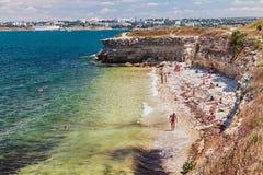 取暖在Chersone古城的一个狂放的海滩的游人 免版税库存图片