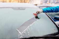 取消冰的妇女从汽车挡风玻璃与玻璃刮板 免版税图库摄影