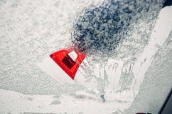 取消冰从汽车挡风玻璃与红色刮板 免版税图库摄影