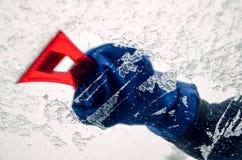 取消冰从汽车挡风玻璃与红色刮板 图库摄影
