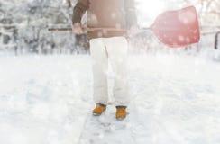 取消在后院的工作者雪与铁锹在降雪期间 免版税库存图片