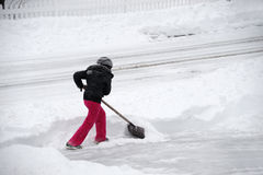 取消在车道的妇女雪由铁锹在飞雪以后 库存图片