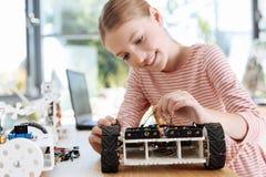 取消导线的十几岁的女孩从一辆机器人车 库存照片