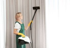 取消尘土的女性管理员从帷幕机智 库存图片