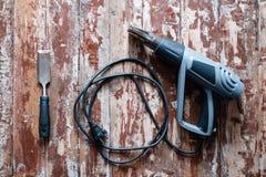 取消油漆从地板与一个热空气开枪修理工具 库存图片