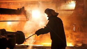 取消炉渣从电感应坩埚熔化炉在冶金植物,辛苦的钢铁工人 库存照片