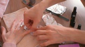 取消胶凝体波兰语从钉子 人在妇女` s钉子上倾吐取消在化装棉的液体,把它放并且包裹箔 股票录像