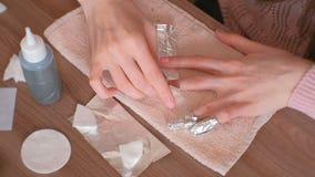 取消胶凝体波兰语从钉子 妇女在钉子上倾吐取消在化装棉的液体,把它放并且包裹箔 关闭 股票录像