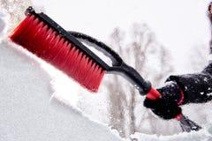 取消雪与刷子从汽车挡风玻璃在冬日 免版税库存图片